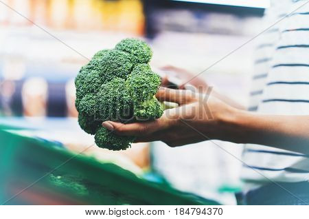 The buyer weighs the green fresh broccoli close up woman shopping healthy food in supermarket blur background female hands buy nature products in store grocery
