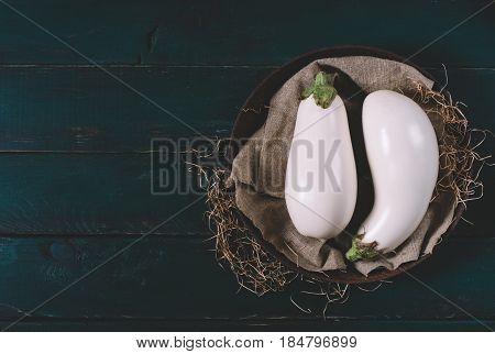 Two white eggplant on textiles with dry grass in a round bowl on wooden mock up vintage black space background of old dark boards top view vegan food on table mock up dieting concept healthy herb