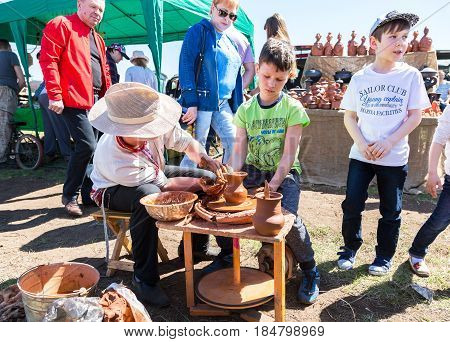 Samara Russia - April 30 2017: Teacher helps his student to work with red clay. Work on the potter's wheel at the outdoors