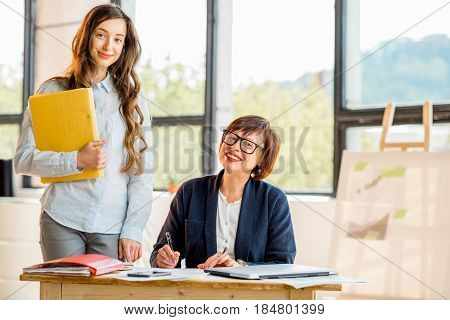 Portrait of a young and older businesswomen working together on documents at the modern office interior