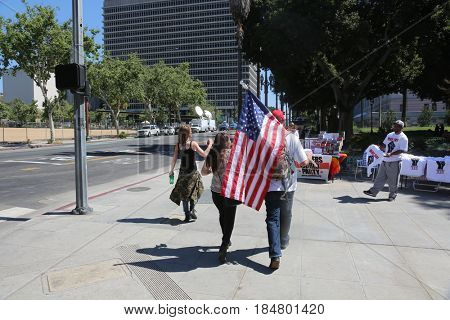 LOS ANGELES California- May 1, 2017: People Wave Signs, Flags, Wear Costumes, Yell, to Support President Trump at a Protest Rally Against President Donald J. Trump on May 1, 2017 in Los Angeles.