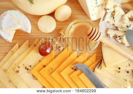 Different types of cheese on wooden table
