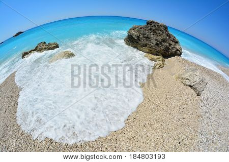 Sunny day on a pebble beach blue turquoise water waves sea foam and a few rocks fisheye seascape