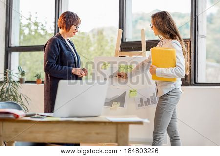 Older and young businesswomen having a conversation near the board with financial charts at the office near the window