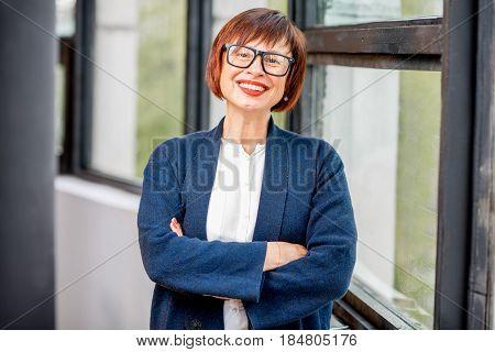 Portrait of an older elegant woman standing indoors near the window