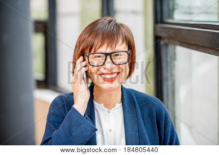 Older and elegant businesswoman talking phone standing indoors near the window