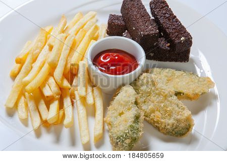 Fresh Beer Snacks Assortment On A White Plate. French Fries, Croutons And Zucchini