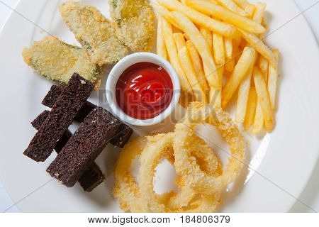 Fresh Beer Snacks Assortment On A White Plate. French Fries, Croutons And Zucchini And Onion Rings.