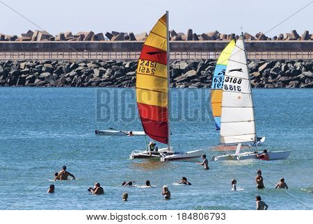 People Swimming Amongst Colorful Yachts In Sea