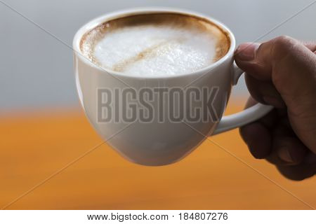 People are drinking coffee in a white cup.
