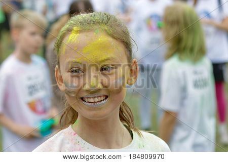 STOCKHOLM SWEDEN - MAY 22 2016: Face of a young beautiful asian woman with yellow and gold color dust in her face in the Color Run Event in Sweden May 22 2016