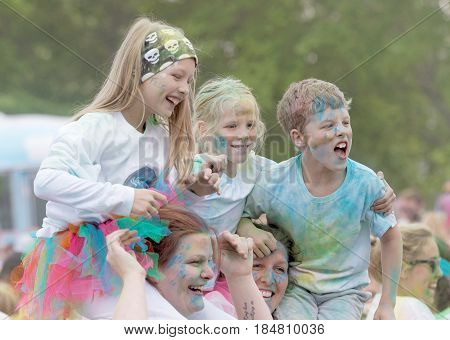 STOCKHOLM SWEDEN - MAY 22 2016: Smiling young children covered with blue paint teir parents shoulders in the Color Run Event in Sweden May 22 2016