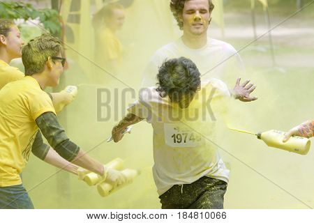 STOCKHOLM SWEDEN - MAY 22 2016: Smiling boys getting squirted with yellow color dust in their face and clothes in the Color Run Event in Sweden May 22 2016