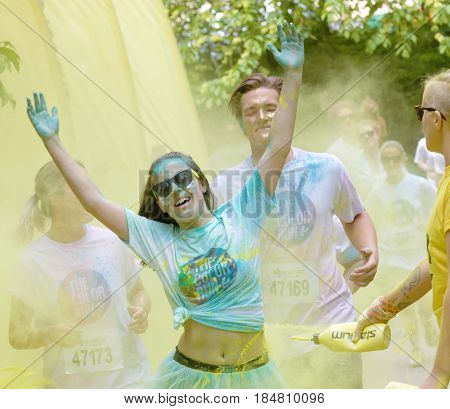 STOCKHOLM SWEDEN - MAY 22 2016: Smiling teenagers covered with yellow and blue color dust running in the Color Run Event in Sweden May 22 2016