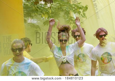 STOCKHOLM SWEDEN - MAY 22 2016: Teenagers with yellow color dust in their face and arms up in the Color Run Event in Sweden May 22 2016