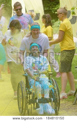 STOCKHOLM SWEDEN - MAY 22 2016: Smiling woman in wheelchair covered with yellow color dust in the Color Run Event in Sweden May 22 2016