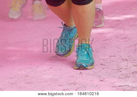 STOCKHOLM SWEDEN - MAY 22 2016: Running shoes on ground covered with pink color dust in the Color Run Event in Sweden May 22 2016