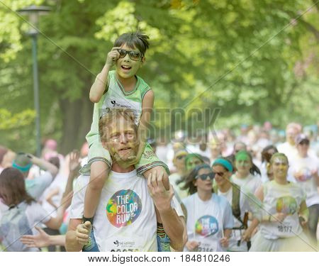 STOCKHOLM SWEDEN - MAY 22 2016: Young boy with green paint in his face on his fathers shoulders in the Color Run Event in Sweden May 22 2016