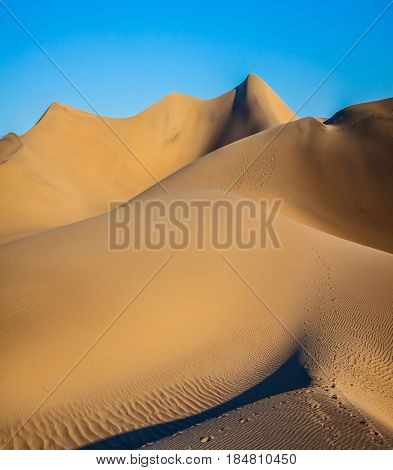 Sunny morning in a picturesque part of Death Valley, USA. Bizarre twists of orange sand dunes. Mesquite Flat Sand Dunes