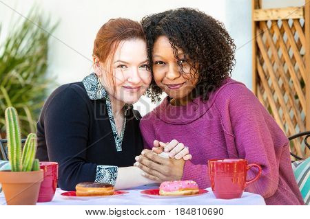 Female Couple Sitting At Table Together