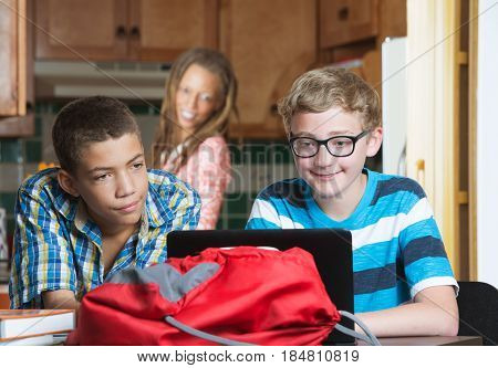 Mother Watching Son And Friend Do Homework