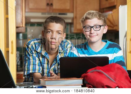 Pair Of Friends With Books And Laptop In Kitchen