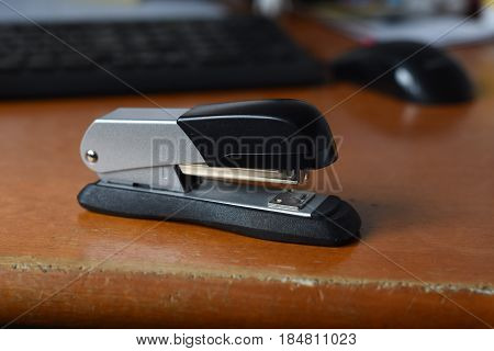 stapler on the desk with computer in the background