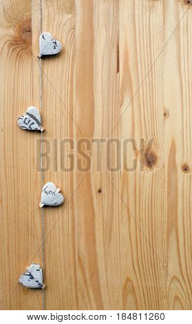 Four hearts with clothes pegs on a cord on wood