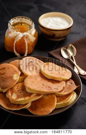 Homemade pancakes with peach jam and sour cream on black background.