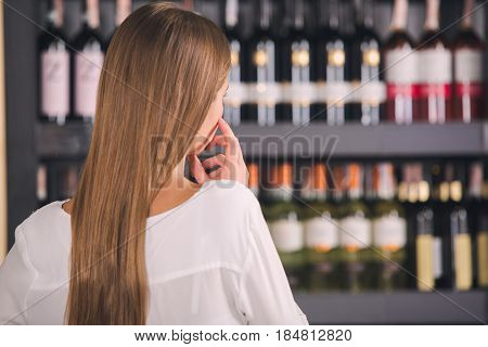 Somellier young elegant female in a wine store professional