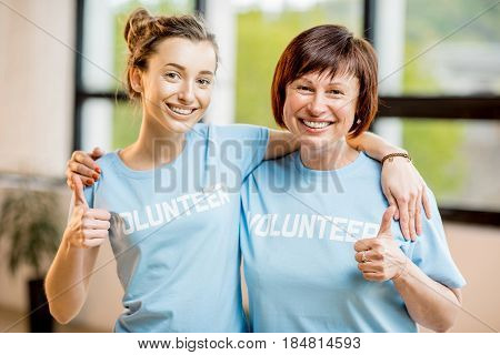 Portrait of an older and young female volunteers in blue t-shirts standing together at the office