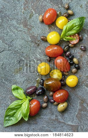 Food background, varieties of heirloom tomatoes and olives with basil, top view over slate.