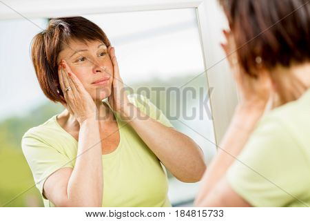 Sad older woman looking at her face into the mirror worried about the wrinkles