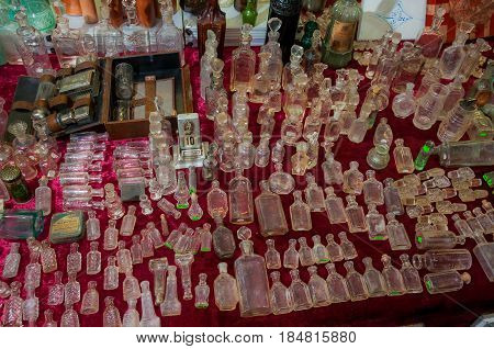 Moscow, Russia - March 19, 2017: Table at the flea market with empty antique bottles and flacons for alcohol, pharmacy and perfumes of various sizes and colors