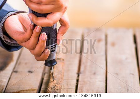 A closeup of a hardworker man drilling a wood stick with his drill on a wooden background.