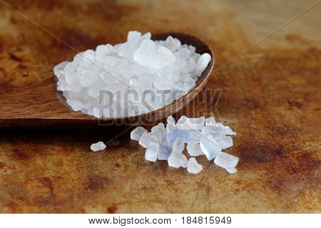 Iranian food Persian blue salt crystal macro view. Mineral saline sodium chloride from. Organic food condiment wooden spoon, aged rusty background. Shallow depth field.