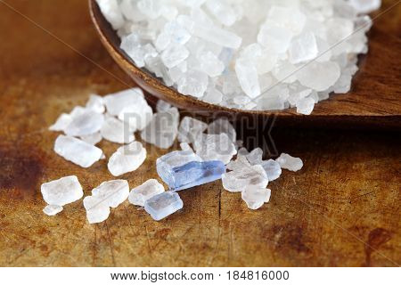 Persian blue salt crystal macro view. Mineral saline sodium chloride from Semnan Iran. Organic food condiment wooden spoon, aged rusty background. Shallow depth field.