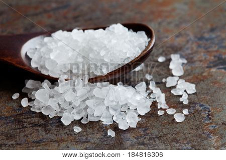 Sea salt condiment macro view. Natural mineral flavoring food preservative, Saline sodium chloride white crystal in wooden spoon, aged background. Shallow depth field.