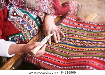 Handmade traditional colorful wool. Peru woman make alpaca textile close-up