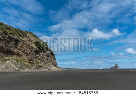 Auckland New Zealand - March 2 2017: Wide shot of black sand Karakare Beach under blue cloudy sky with Te Kaka Whakaara Rock (Watchman) in the surf of Tasman Sea far away. Rocky cliff.