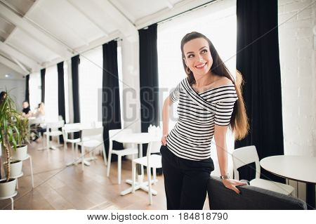 Happy lady at home looking outdoors through a window. Cheerful woman smiling and looking away