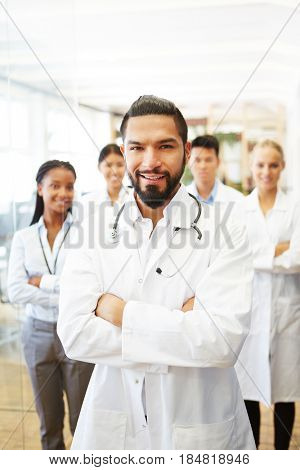 Confident man as doctor with successful team in hospital