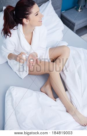 Woman in bathrobe after bath in bedroom