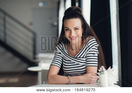 Happy lady in a cafe smiling for the camera. Cheerful woman sitting at the table and looking at the camera