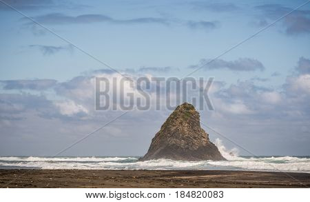 Auckland New Zealand - March 2 2017: Wider shot of black sand Karakare Beach under blue cloudy sky with Te Kaka Whakaara Rock (Watchman) in the surf of Tasman Sea.