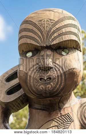 Auckland New Zealand - March 2 2017: Face closeup of wooden sculpture of Te Kawerao A Maki the spiritual guardian (Manawhenua) of Karakare Beach. Blue sky.