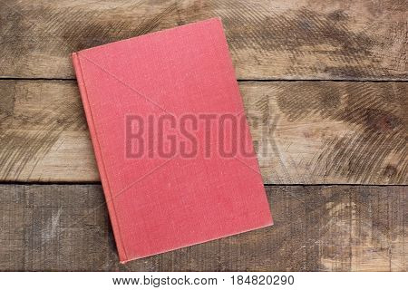 red book on the background of rough planks. view from the top.