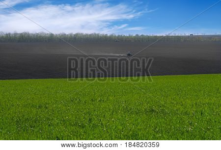 The Tractor Cultivates The Field. Rural Rural Background. Panoramic View Of The Spring Landscape On