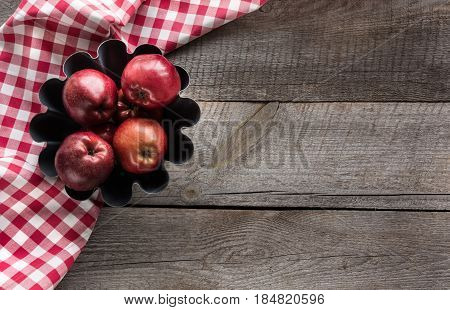 Ripe red apples in baking form on wooden board with red checkered napkin.