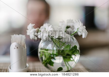 Vase with flowers in a cafe, white daisies, in the background people